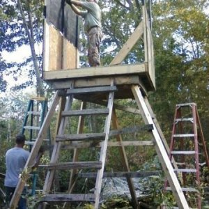 Uncle and dad building an elevated stand over looking a corn field.